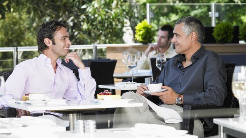 Happy businessmen conversing at outdoor cafe.