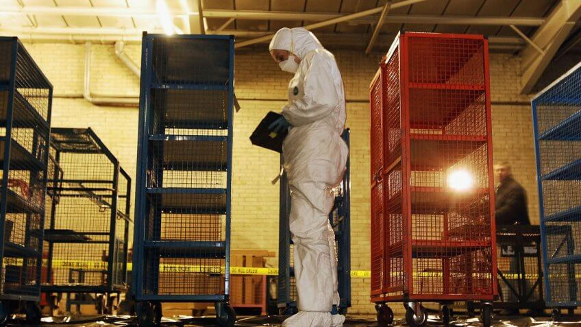 UNSPECIFIED - FEBRUARY 25:  A police forensic officer inspects money cages February 25 2006 that were used to store banknotes that were stolen from the Securitas Depot in Tonbridge Kent last week.