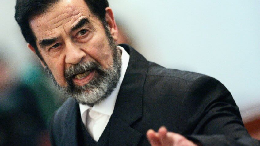 BAGHDAD, IRAQ - FEBRUARY 14: Former Iraqi President Saddam Hussein addresses the court of the Iraqi High Tribunal inside the heavily fortified Green Zone on February 14, 2006 in Baghdad, Iraq.