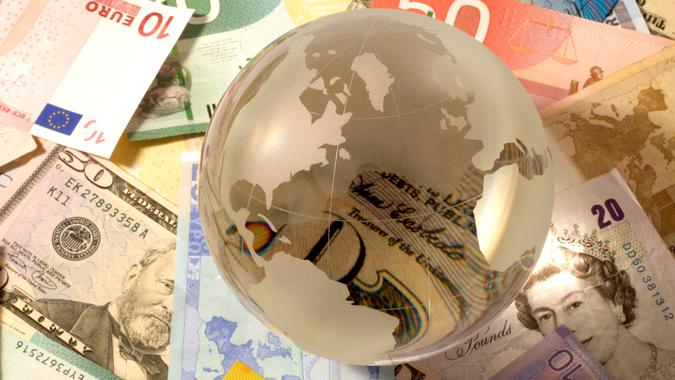 Glass globe on variety of banknote.