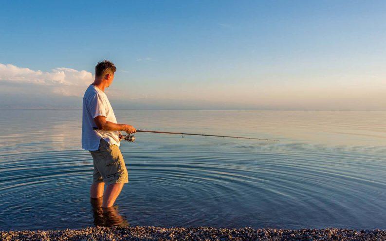 man fishing water blue