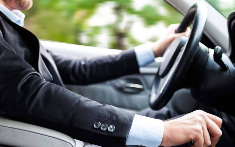 man suit driving car fast
