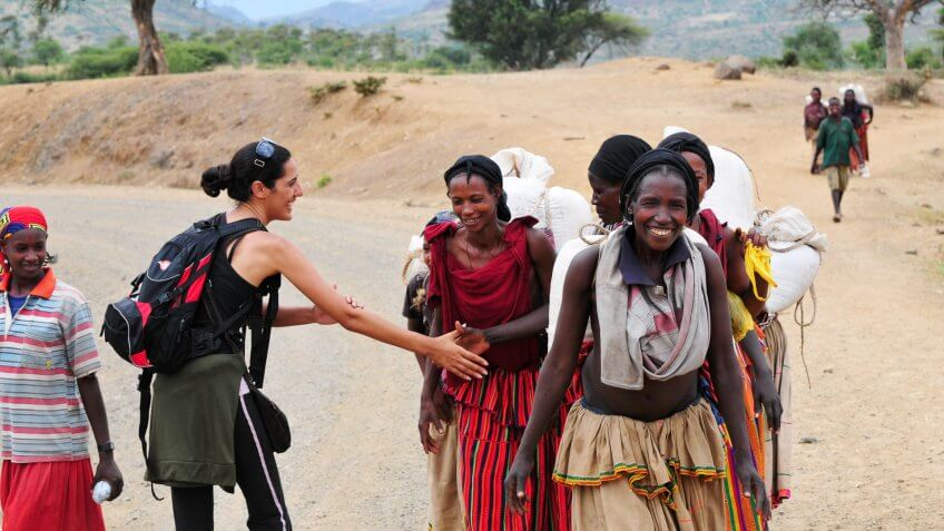 """Konso, Ethiopia - August 9, 2010: An Israeli woman traveling in Ethiopia greets local villagers with a culturally correct handshake, in which one's left hand rest on the inside of the elbow during the handshake."