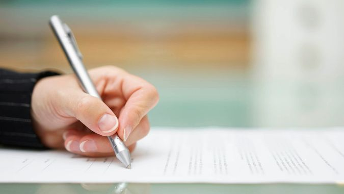 woman signing paperwork filling document