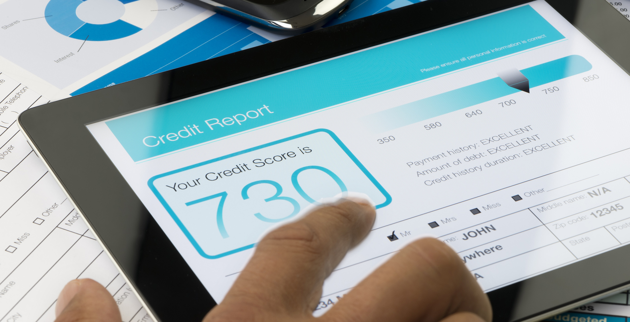 credit report on a digital tablet with paperwork.