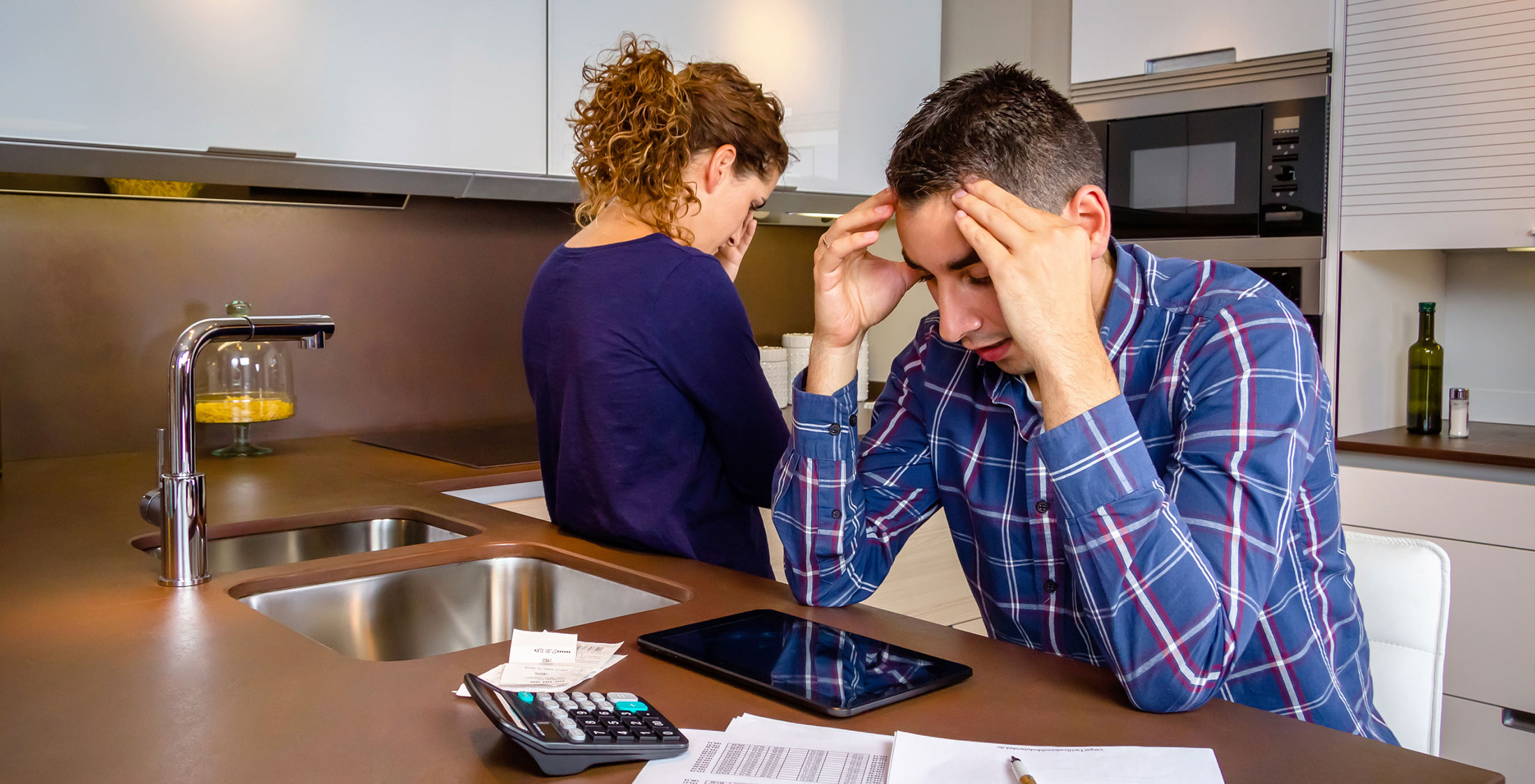 man woman kitchen fighting headache taxes ipad paperwork