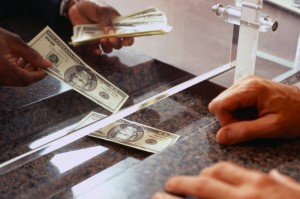 Bank Teller Counting Money for Customer