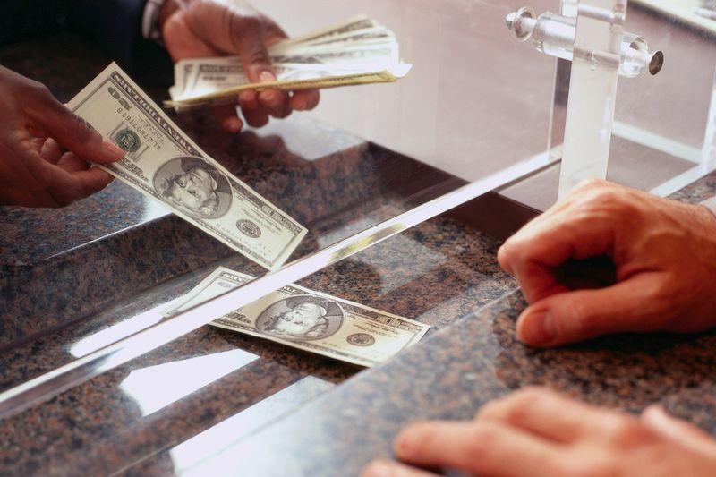 Bank Teller Counting Money for Customer