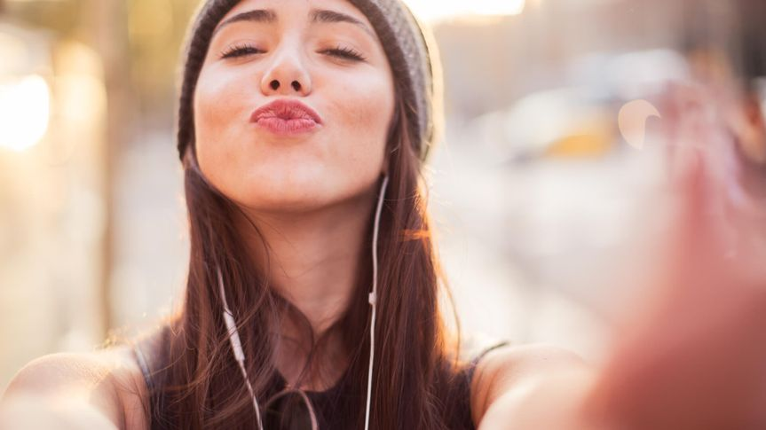 woman with earphones taking a selfie