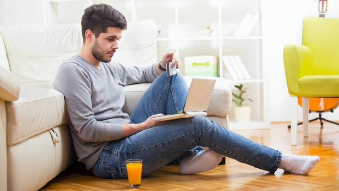 Handsome man holding credit card and using laptop for online shopping - indoors.