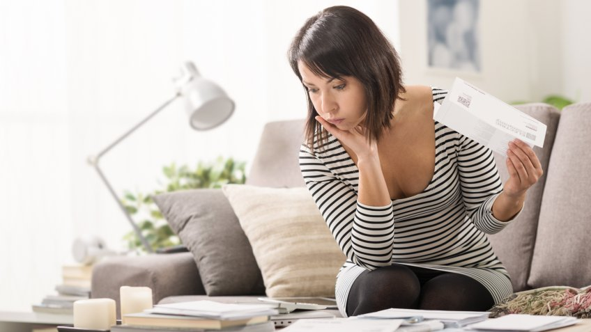 Stressed woman at home checking expensive electricity and household bills, home finance concept.