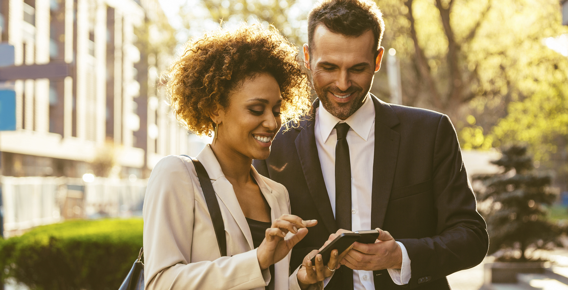 Outdoor portrait of cheerful businessman and businesswoman using a smart phones.