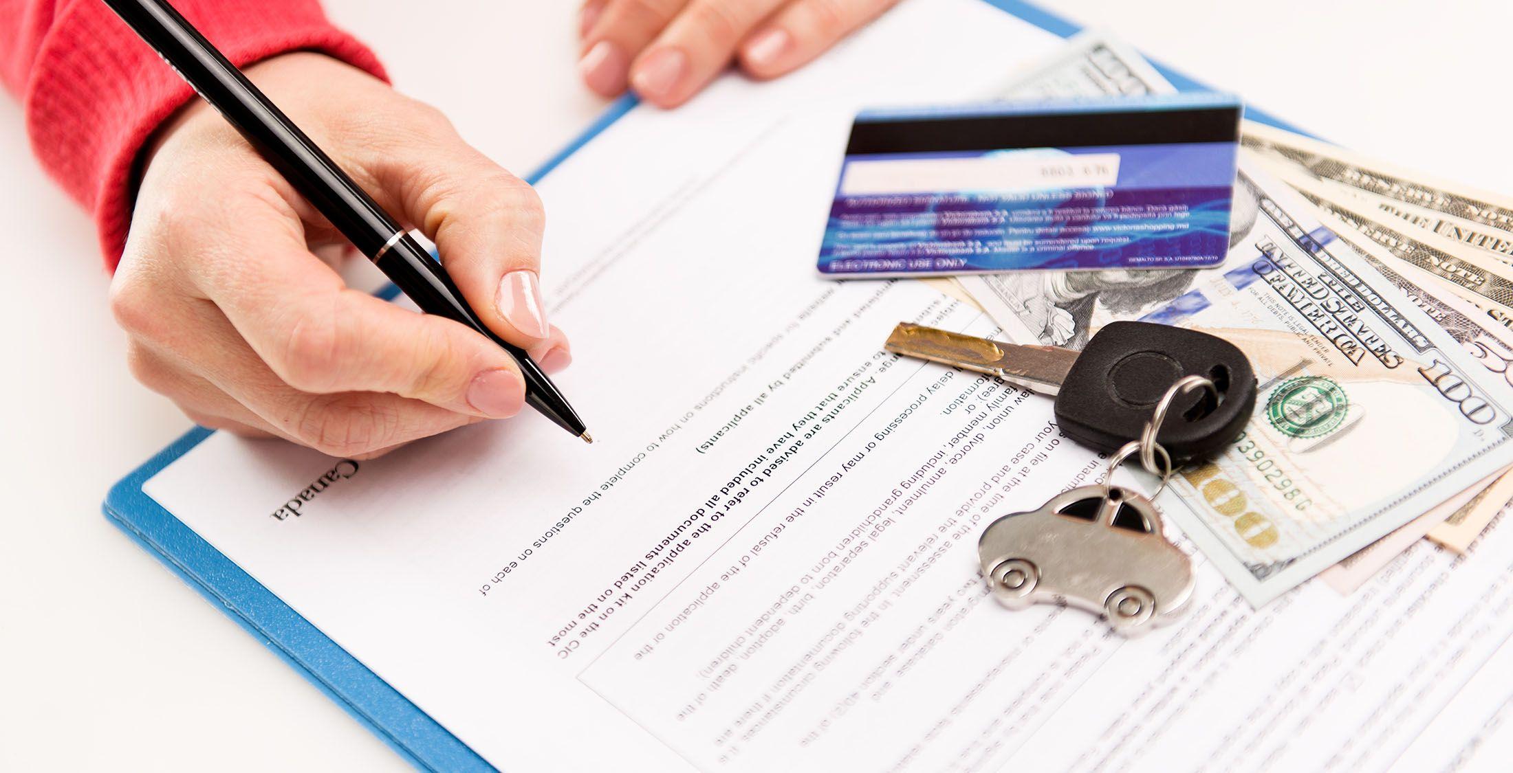 hand signing form credit card cash car keys