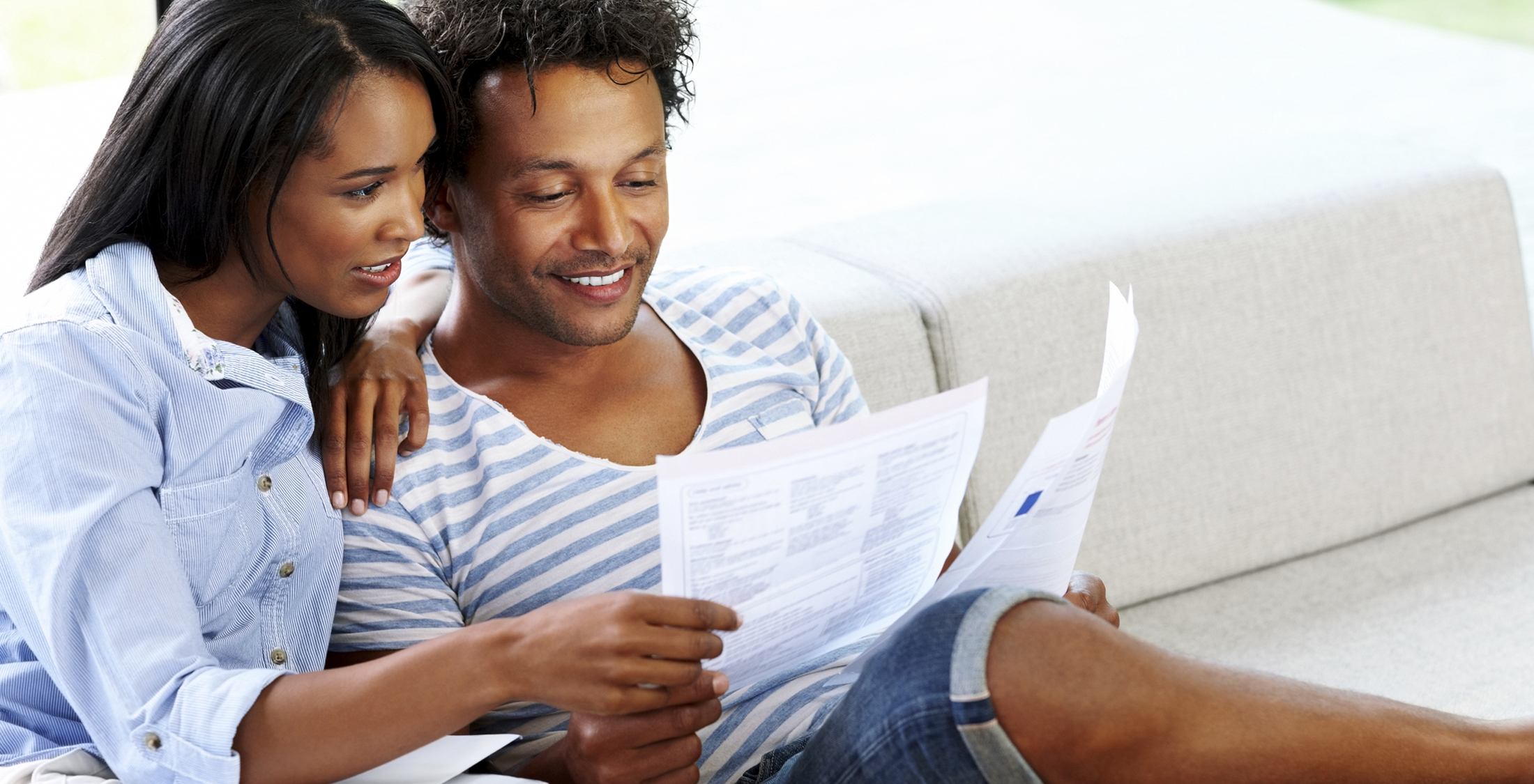 Young couple sitting on sofa reading a financial bill at home