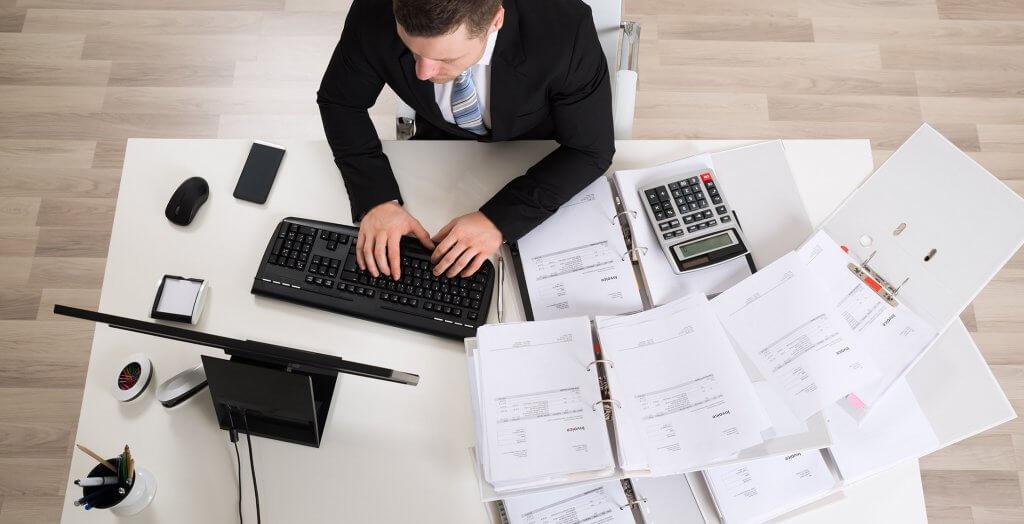 overhead shot of man on desktop computer with binders of finances