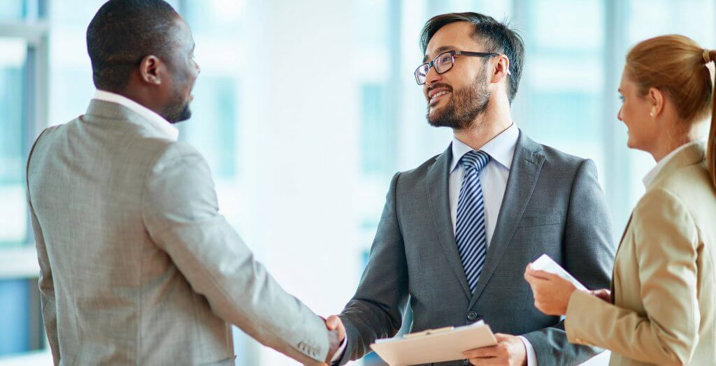 businessmen shaking hands with woman watching
