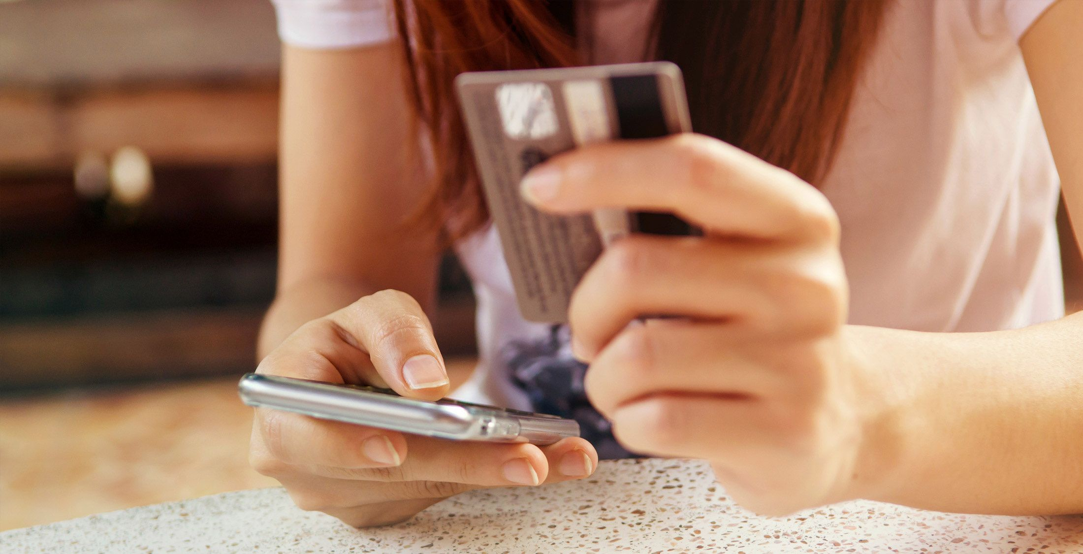 girl paying with credit card on mobile cell phone mobile banking