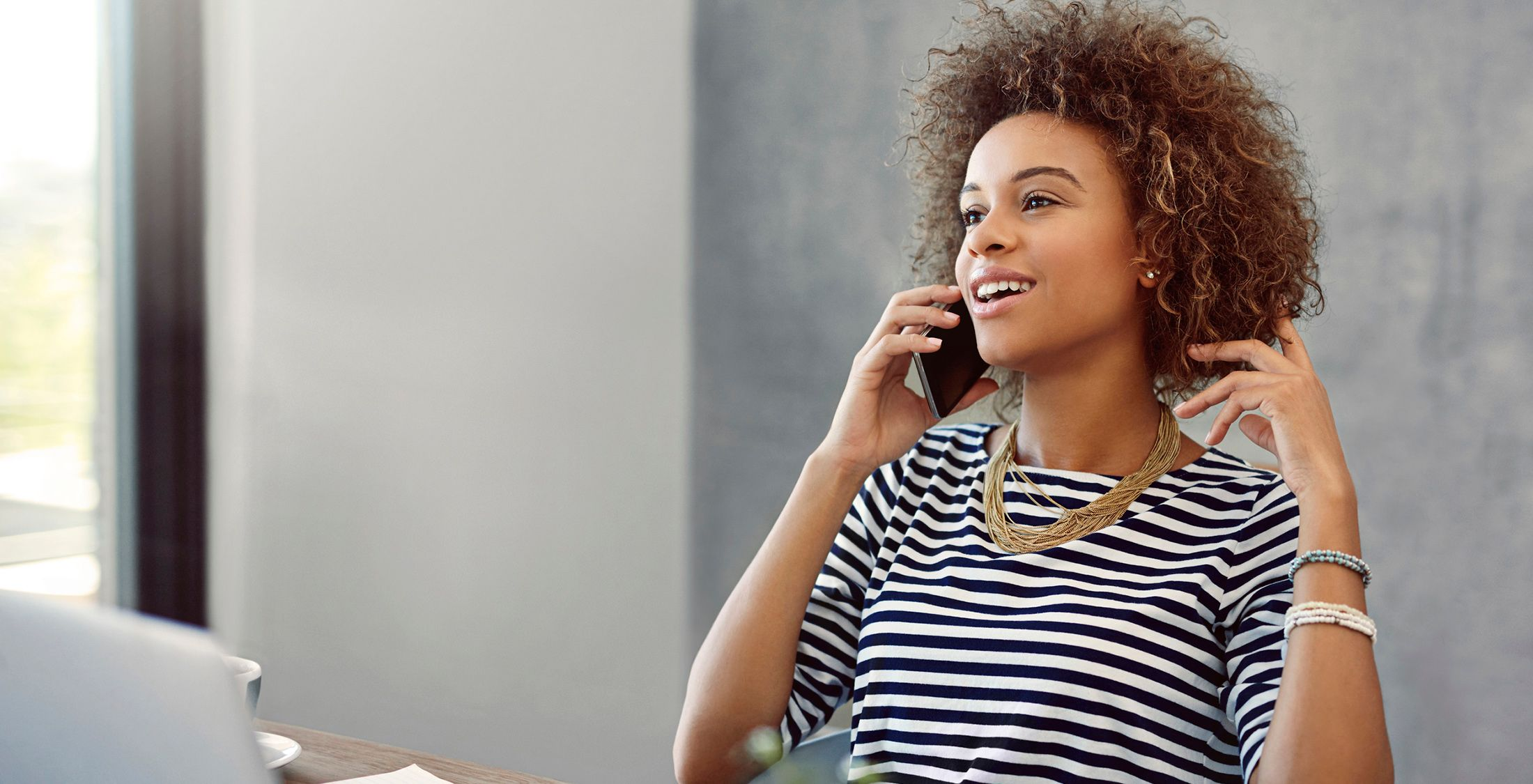 young woman talk on the phone while sitting at a desk at home