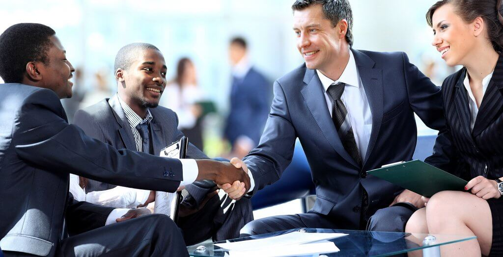 business people meeting outside shaking hands