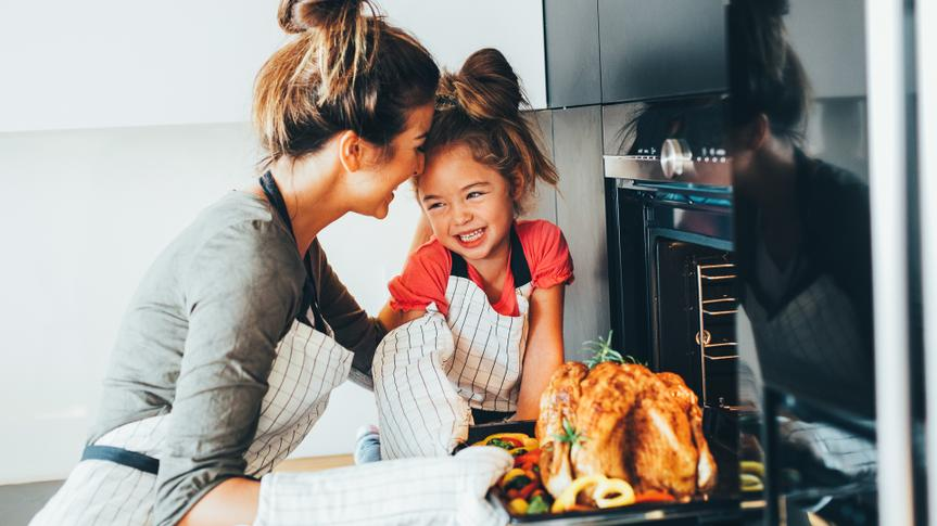 Little girl watching her mother taking the turkey out of the oven.