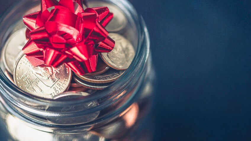 Christmas money jar with American currency and topped with bow.