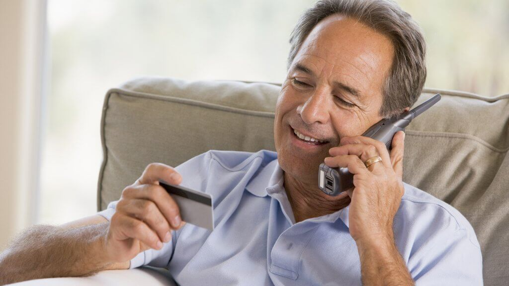 man on the phone reading credit card information