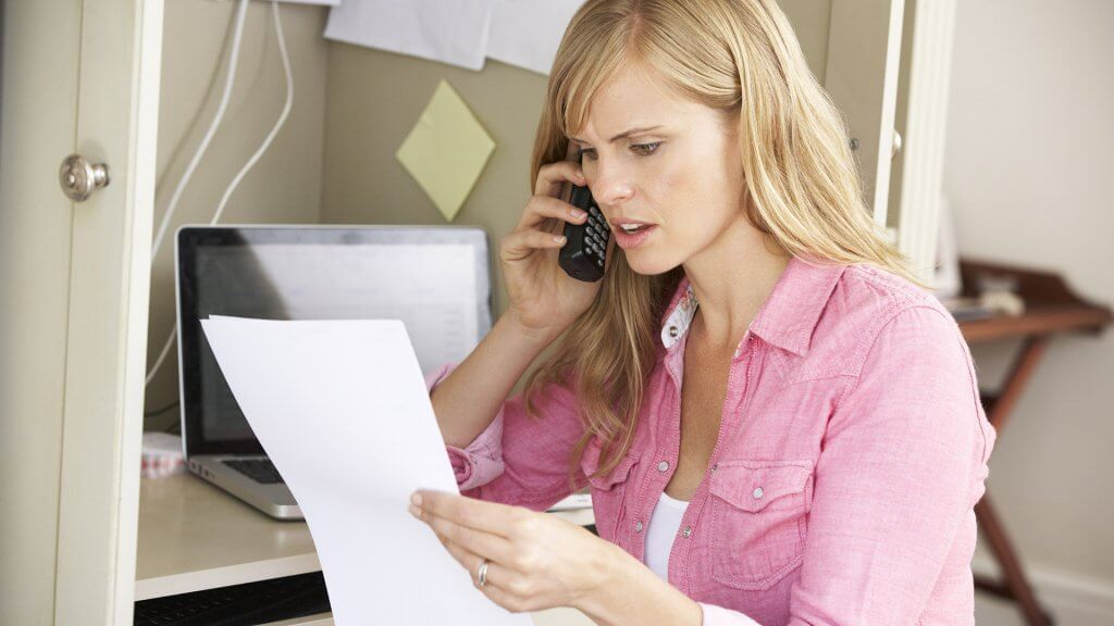 woman on the phone reading business paper