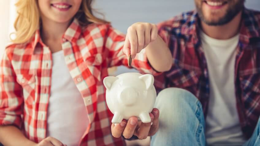 Young woman is putting a coin into a piggy bank that a man is holding.