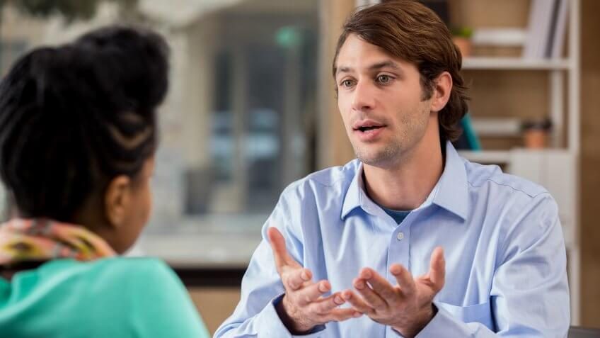 Mid adult Caucasian male psychiatrist gestures while talking with female African American client.