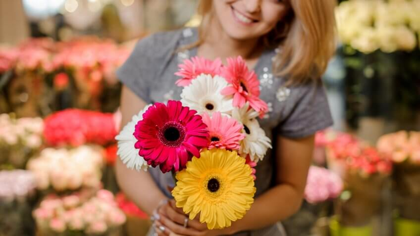woman holding a bouquet of daisies
