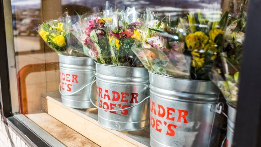 Fairfax, USA - January 18, 2017: Buckets of flowers with Trader Joe's signs viewed from outside of store.