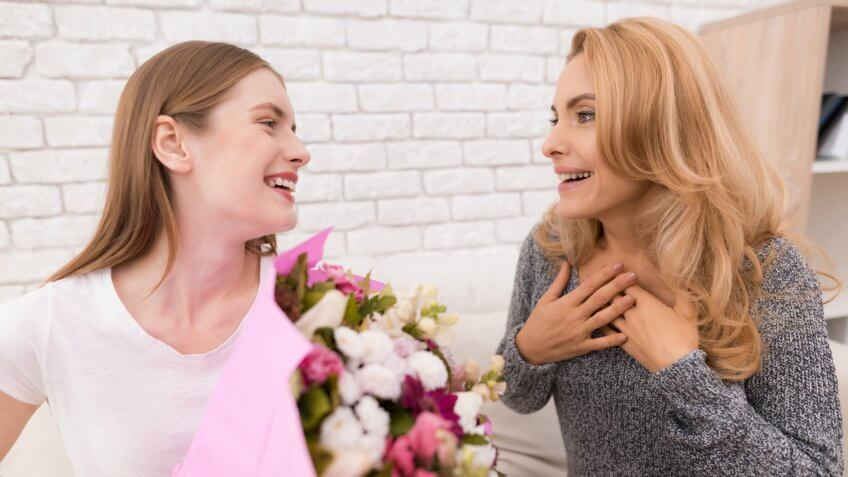 woman giving another woman a bouquet of flowers