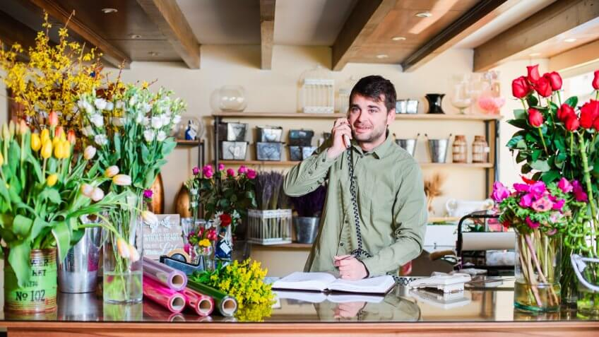 male florist speaking with client on the phone