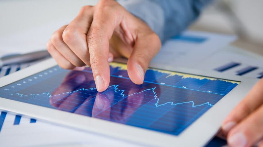 man watching stock market graphs on a tablet