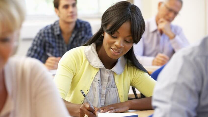 young woman taking notes in a class setting