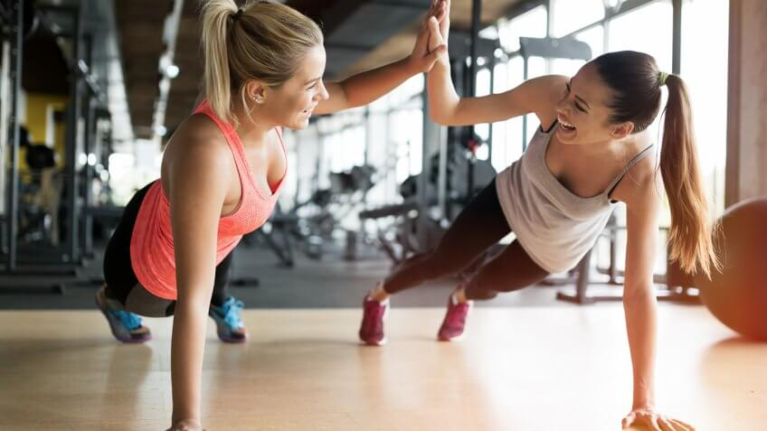two women high-fiving while doing planks