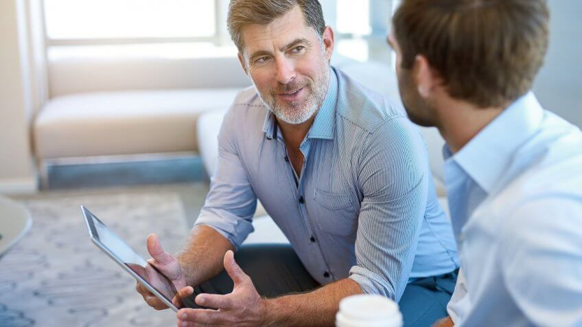 man holding ipad tablet speaking to another man