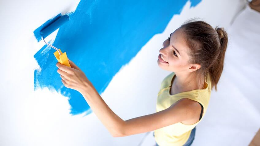 woman painting the walls blue