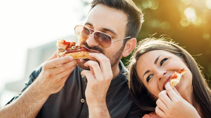 young couple enjoying slices of pizza