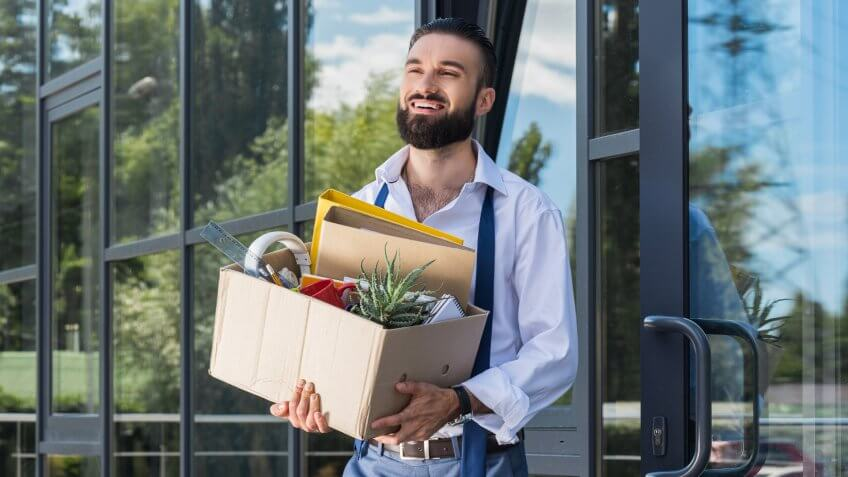 happy businessman with cardboard box walking out office building, quitting job concept.