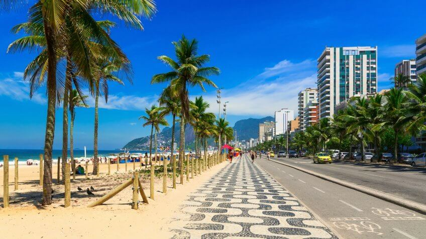 How Much to Tip When Traveling to These 25 Countries, Ipanema beach with mosaic of sidewalk in Rio de Janeiro. Brazil