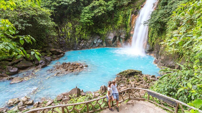 Tourist couple looking at Rio Celeste waterfall, Tenorio Volcano National Park, Guanacaste, Costa Rica.