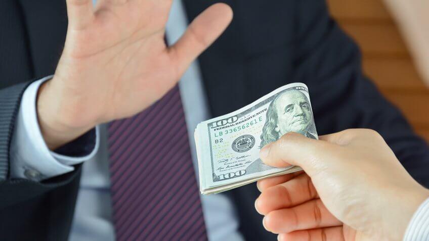 Close up of man refusing stack of hundred dollar bills