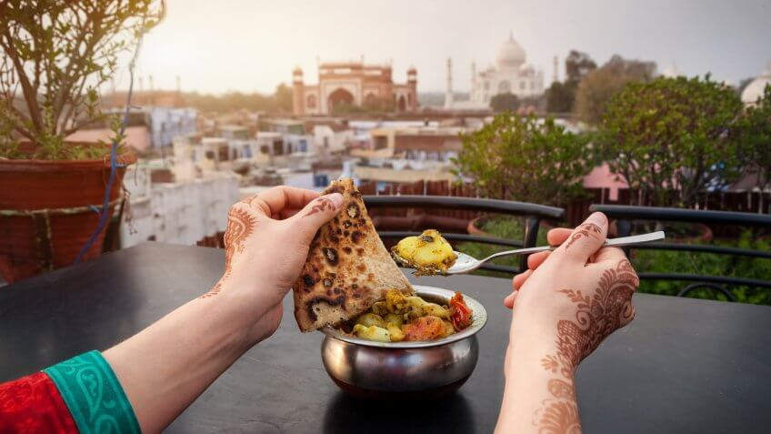 How Much to Tip When Traveling to These 25 Countries, India, Uttar Pradesh, Woman eating traditional Indian food in rooftop restaurant with