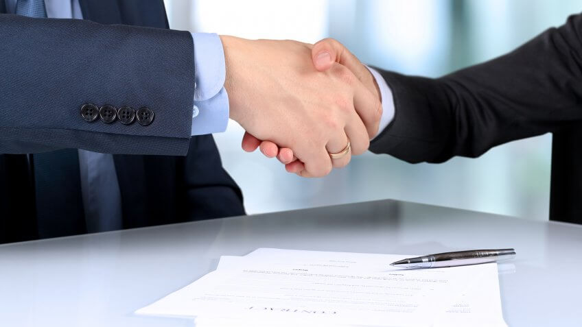 Close up of man and woman shaking hands over documents