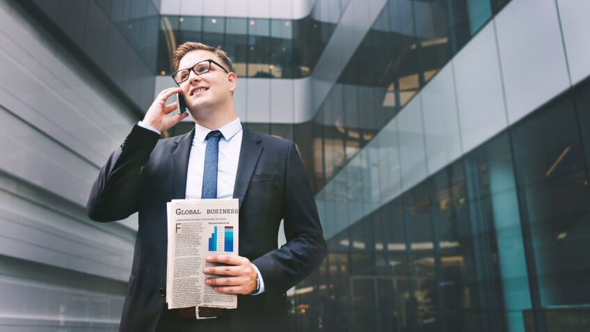 Businessman with newspaper talking on phone