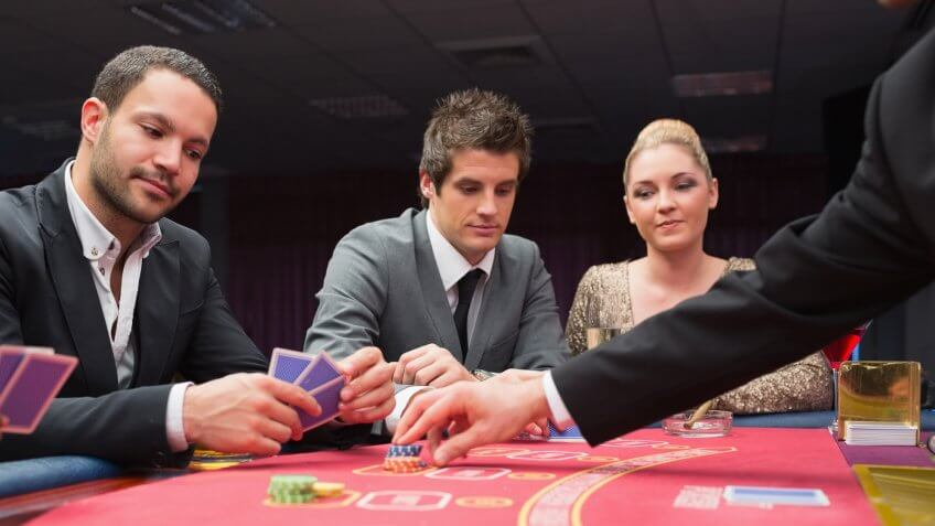 Two men and one woman playing poker