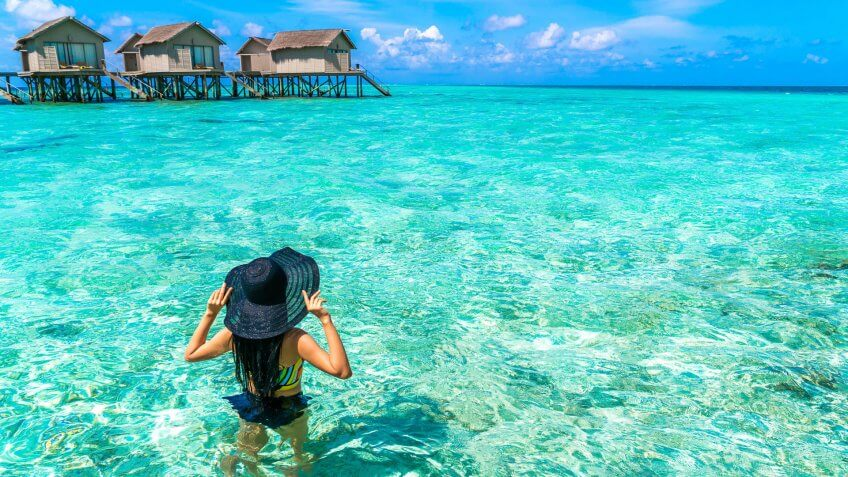 How Much to Tip When Traveling to These 25 Countries, Portrait of happy young woman at beautiful water villa at Maldiv