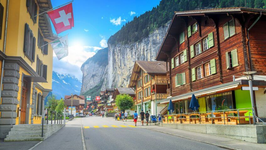 Bernese Oberland, Europe, How Much to Tip When Traveling to These 25 Countries, Principal street of Lauterbrunnen with shops, Switzerland, hotels, swiss flags and stunning Staubbach waterfall in background, terraces