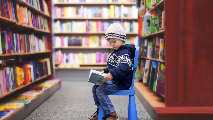 child sitting in a library reading a book